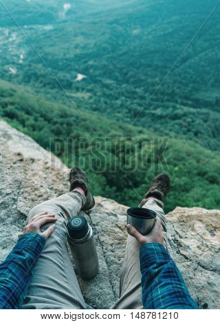 Female hiker sitting on cliff and drinking tea from thermos in summer mountains point of view