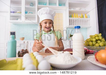 Excited girl is preparing flour for baking. She is standing neat table in kitchen and laughing