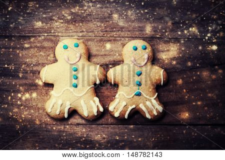 Christmas Card with gingerbread man cookies decorations and falling snow with copy space over dark wooden background