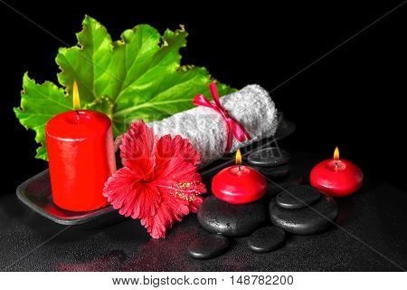 Beautiful Spa Concept Of Red Hibiscus Flower With Dew, Candles, Green Leaf And Rolled Towel Tied Wit