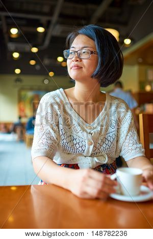 SHENZHEN, CHINA - SEPTEMBER 07, 2016: indoor portrait of a woman at Starbucks in Shenzhen. Starbucks Corporation is an American coffee company and coffeehouse chain.