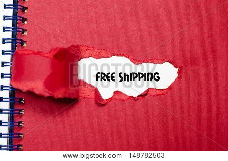 The word free shipping appearing behind torn paper