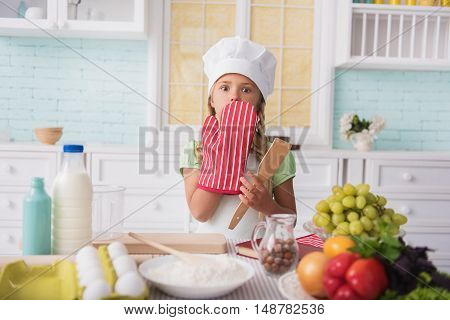 Oops. Cute little girl made mistake in cooking. She is covering mouth with hand in potholder. Child is standing and looking at camera with fear