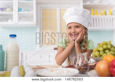 Happy girl is satisfied with cooking. She is looking forward with proud and smiling. Kid is standing near table and leaning head on hands in kitchen