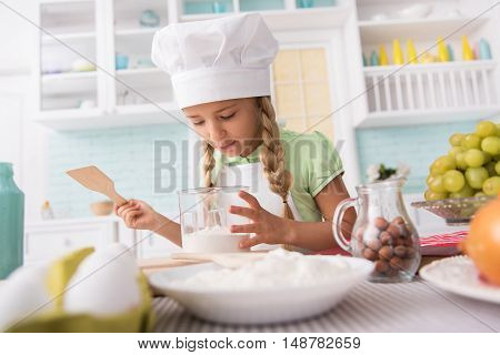 Cheerful girl is preparing batter in kitchen. She is standing in kitchen and looking into utensil with interest