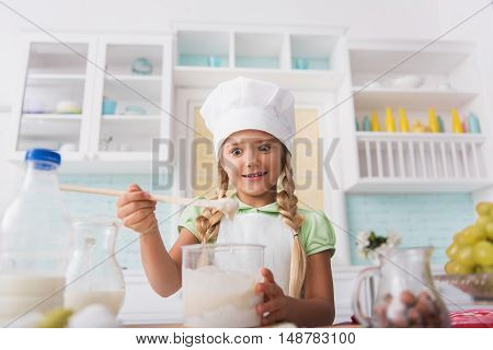 Excited child is making batter with interest. She is standing and staring at dough with surprise. Kid is smiling