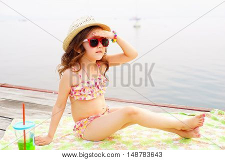 little girl in red sunglasses and bathing suit with sparkling water looks into the distance on a pier near the lake