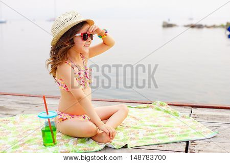 little girl in red sunglasses and bathing suit with sparkling water laughing at the pier near the lake