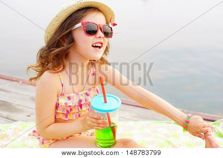 little girl in red sunglasses and bathing suit with sparkling water resting on the pier