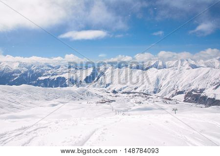 Bird view on the ski village in valley. Background of snowboard resort from the high peak. Winter season for advertising or billboard