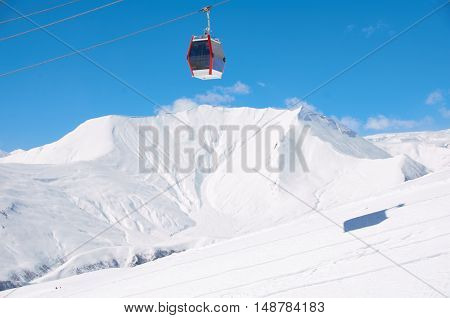 Cable lift for skiers or snowboarders in brigth day on ski resort with blue sky and white mountains background. Copy space for a text. Red car. cabinet for athletes