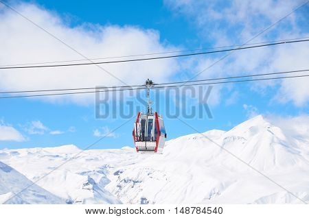 Winter resort concept. Red cabine lift for tourists ski and snowboarders with bright sky and white mountains.