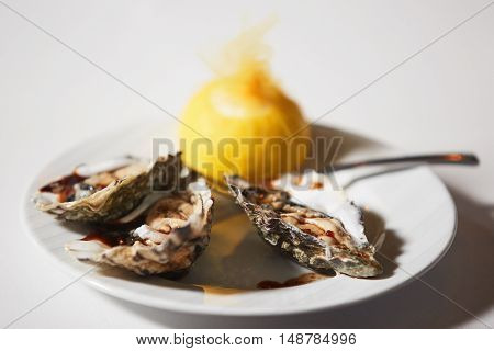 Fresh oysters platter with sauce and lemon in a restaurant
