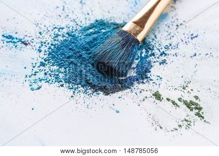 Blue, purple, green eyeshadow scattered on white background