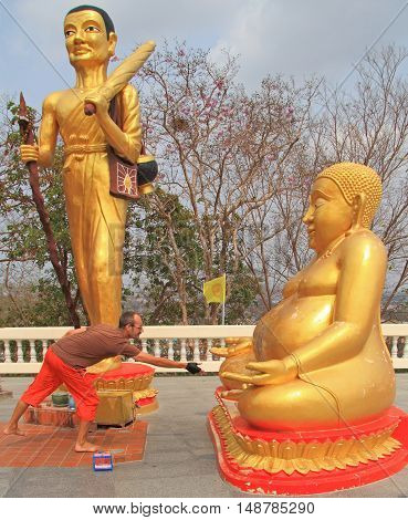Pattaya, Thailand - March 21, 2015: man is throwing a coin to the stomach of religious statue on the hill in Pattaya Thailand