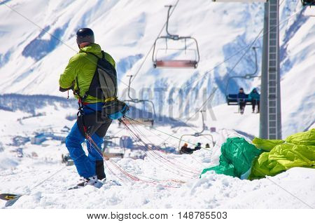 Ski paragliding prepairing for fly. Extreme sport in high mountains on snowboard resort. Happy sport and health life.