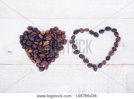 Coffee beans in heart shape on wooden background. Top view. Coffee lover concept.