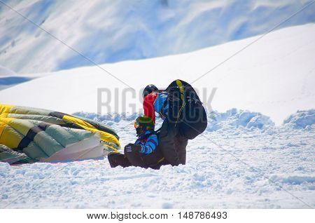 Paragliders tandem after landing in winter snow mountains. Extreme sport health weekend or holiday