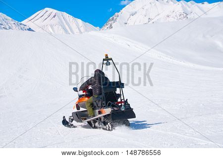 man drive snowmobile in mountains. ski resort staff. extreme driving with perfect winter landscape. Snow riding to the peak.