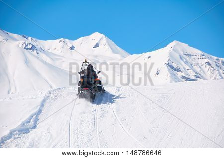 Extreme drive in mountains by snowmobile. Sport healthy weekend in snowy valley with fresh air. Man rush to the rescue to ski or snowboard crush.