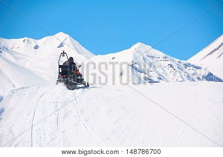 man drive snowmobile in mountains. ski resort staff. extreme driving with perfect winter landscape. Snow riding to the peak. Copy space for text