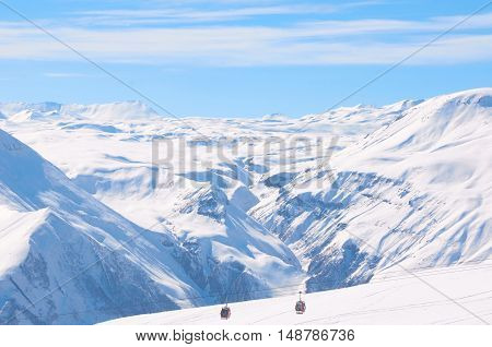 Cable car on ski resort with blue sky background. Concept of snowdoard hobby. Place for rest and relax in snow season in mountains. Copy space for advertising or logo.