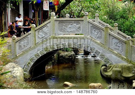 Ping Le China - September 28 2010: A traditional Chinese bridge with carved bas relief panels spans a stream running through the center of the town's main street