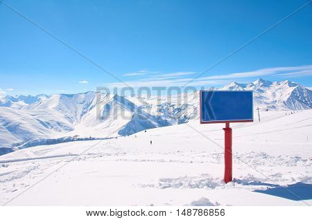 Bird view on the ski village in valley. Background of snowboard resort from the high peak. Winter season for advertising or billboard. Copy space on the sign.
