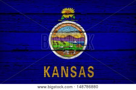 Kansas US State grunge wood background with Kansan flag painted on aged wooden wall.