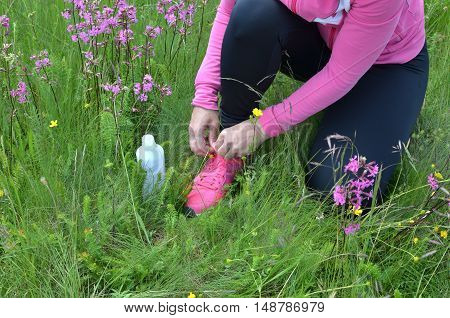 Close up of woman tying shoelaces and preparing for jogging in nature