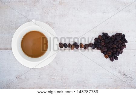 Coffee cup and coffee beans in heart shape on wooden background. Top view. Coffee lover concept.