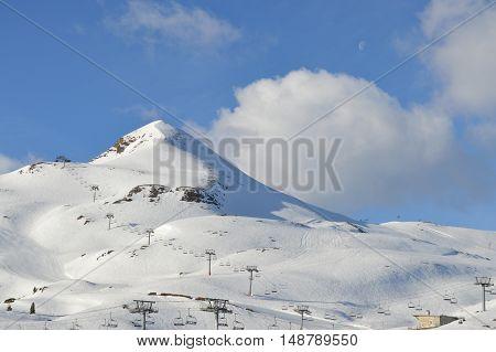 La luna en pleno día decorando el paisaje nevado