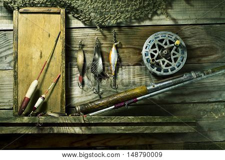 Set for fishing on the shelf. On a wooden background
