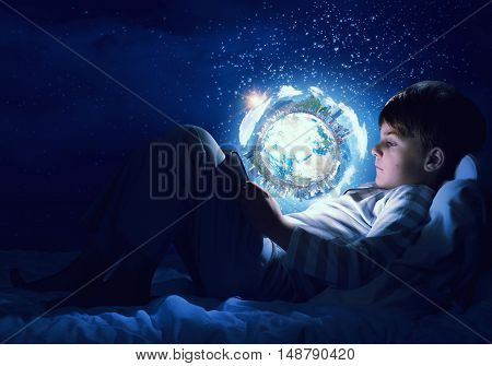 Teenage boy in pajamas lying in bed using tablet pc. Elements of this image are furnished by NASA