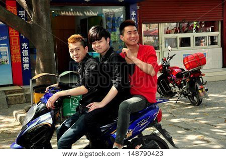 Pixian China: March 27 2013: Three Chinese youths riding a motorcycle along the town's main street