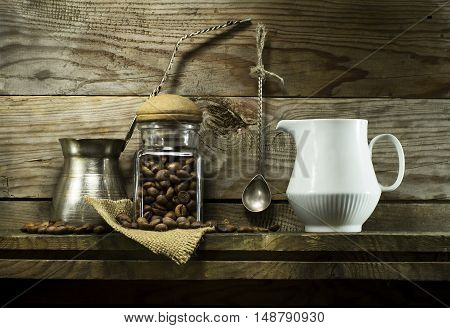 Coffee beans in a glass jar and spoon on a shelf. On a wooden background
