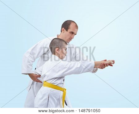 Coach adjusts athlete in karategi on the light background