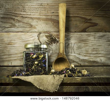 Dry tea in a glass jar with a spoon on a shelf. On a wooden background