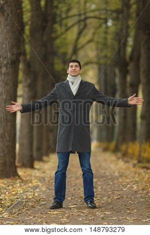 Portrait in full growth young man in gray coat with outstretched hands on alley in autumn park, looking up