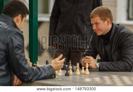 Two young men in black jackets playing chess in gazebo one of them smiling