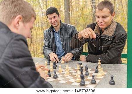 Three young men in black jackets sit in gazebo, two of them playing chess, focus on right man