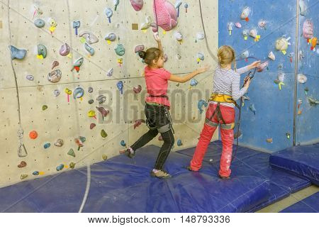 Rock climbing. Two girls in indoor climbing center in safety equipment are jumping on mat.
