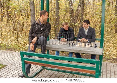 Three young men sitting in gazebo for game of chess in autumn park