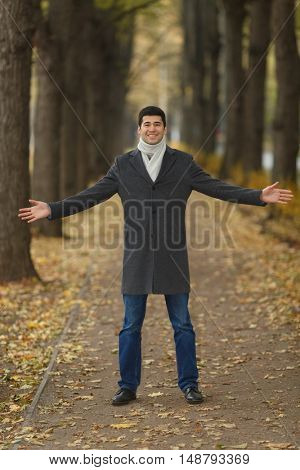 Portrait in full growth young man in gray coat with outstretched hands on alley in autumn park