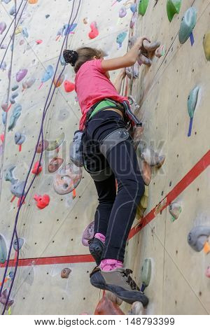 Rock climbing. Young girl with equipment rises on specially-equipped wall for climbers.