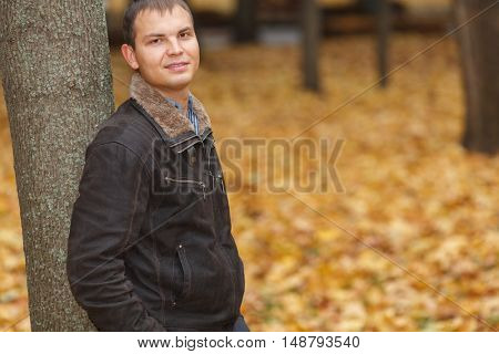 Portrait of young man in black jacket autumn park, leaning back against tree trunk
