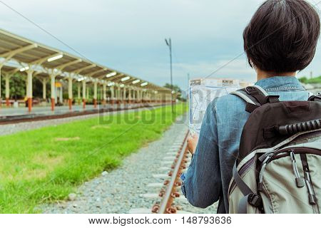 Young woman traveler with backpack look searching location map at the train station Travel concept soft focus vintage tone