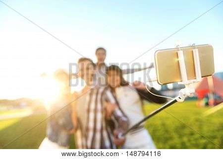 selective focus of smartphone on selfie stick while blurred people smling