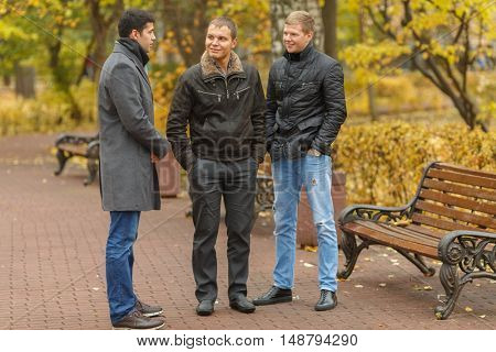 Three young men in black jackets standingnear park bench and talk