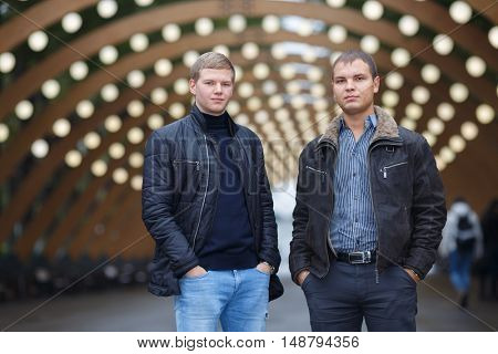 half length portrait of two young man in black jacket on background of lights installation main park alley